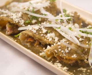 DUCK CARNITAS ENCHILADAS: Gunthorp duck carnitas, spicy chiles torreados, tangy tomatillo sauce infused with smoky mezcal, homemade fresh cheese