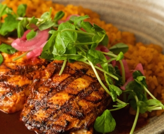 Wood-grilled feature fish, red chile escabeche (ancho, aromatic spices, lime juice, olive oil), achiote rice, Nichols sunflower shoot salad (pickled red onions, lime)