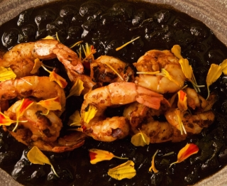 Grilled red chile shrimp, mole de mar (ancho chile, tomatillo, raisins, plantains, bread, sesame, almond, squid ink), braised wild-harvested lambs quarters greens, black beans