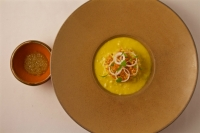 """Slow-cooked Gunthorp chicken, slow-cooked rice porridge infused with squash blossoms, crema & rich chicken stock, crispy chicken skin crumble, roasted serrano """"salsa."""""""