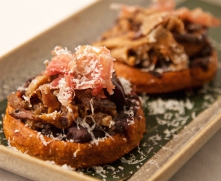 "Sweet potato-infused crispy corn masa boats, mushroom-prosciutto filling (smoky morita, grilled onions), traditional black beans, Frontera's exclusive goat ""bola"" cheese"